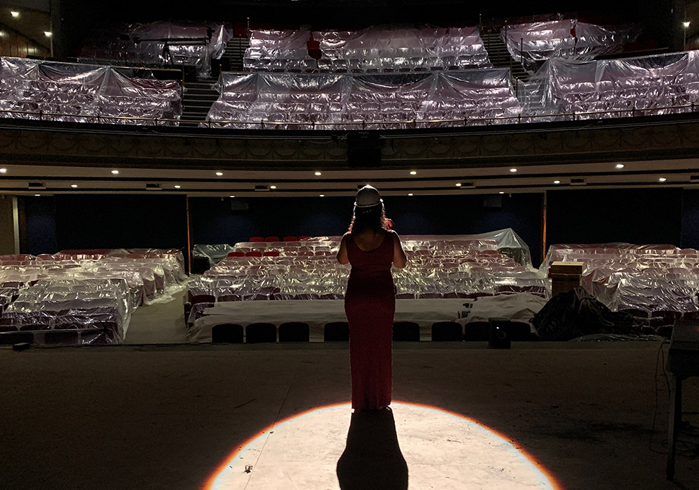 Alexis Gordon stands in the spotlight on the stage, singing to an empty auditorium.