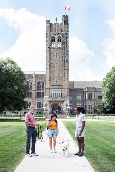 Alan Shepard, Lauren Rebelo, Meisha the golden retriever, and Daniel stand in front of University College before setting out on their walk.