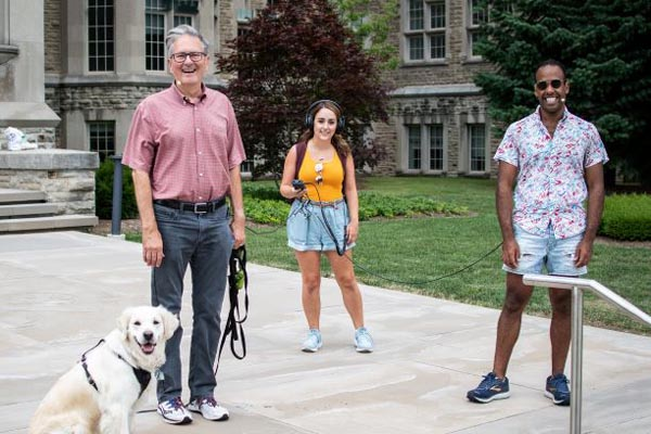 Meisha the Golden Retriever, Alan Shepard, Lauren Rebelo, and Daniel Bennett smile in front of University College as they get ready to walk.