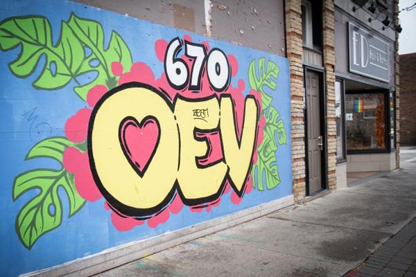 A colourful mural reading '670 OEV' covers the entrance to 670 Dundas St.