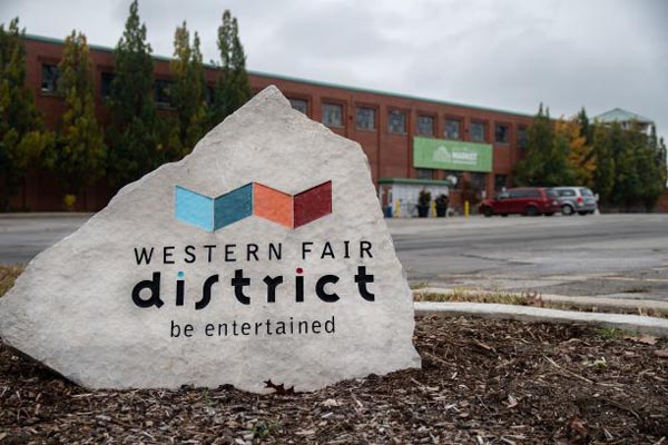 A Western Fair District sign with the market in the background.