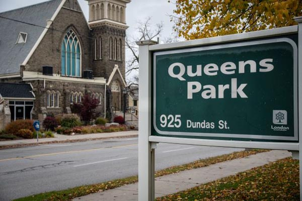 Queens Park sign at 925 Dundas Street, marking an entrance to the park.