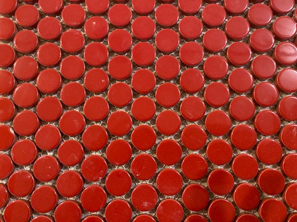 A close-up view of the small, circular red tiles on the feature wall leading into the Auburn Theatre.